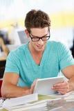 Hombre que usa la tablilla de Digitaces en oficina creativa ocupada Imágenes de archivo libres de regalías