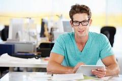 Hombre que usa la tablilla de Digitaces en oficina creativa ocupada Fotografía de archivo libre de regalías