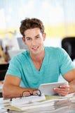 Hombre que usa la tablilla de Digitaces en oficina creativa ocupada Fotos de archivo