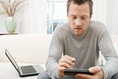 Hombre que usa la tablilla y el ordenador en el sofá en casa. Fotos de archivo