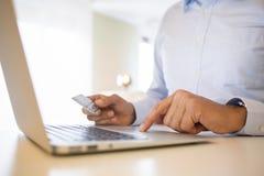 Hombre que usa la tarjeta de crédito y el ordenador portátil, haciendo compras en line.indoor Fotografía de archivo