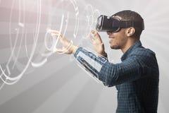 Hombre que usa las auriculares de la realidad virtual Foto de archivo libre de regalías