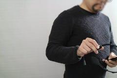 Hombre que usa las auriculares de VOIP con el teléfono elegante, comunicación del concepto, Fotos de archivo