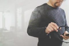 Hombre que usa las auriculares de VOIP con el teléfono elegante, comunicación del concepto, Imagen de archivo libre de regalías