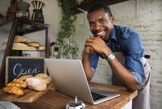 Hombre que usa los dispositivos para la orden de negocio en línea en la panadería imagenes de archivo