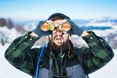 Hombre que usa los prismáticos en la montaña nevada Fotos de archivo