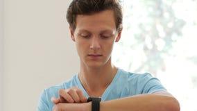 Hombre que usa los usos de Smartwatch metrajes