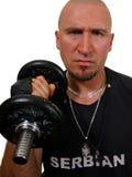 Hombre que usa pesa de gimnasia Imagen de archivo