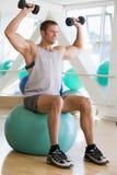 Hombre que usa pesos de la mano en bola suiza en la gimnasia Imágenes de archivo libres de regalías