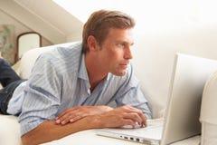 Hombre que usa sentarse de relajación de la computadora portátil en el sofá en el país imagen de archivo