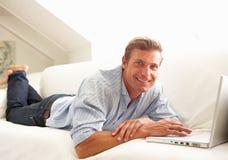 Hombre que usa sentarse de relajación de la computadora portátil en el sofá en el país Imagen de archivo libre de regalías