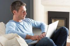 Hombre que usa sentarse de relajación de la computadora portátil en el sofá en el país Fotografía de archivo libre de regalías