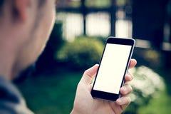 Hombre que usa smartphone con la pantalla en blanco fotos de archivo libres de regalías