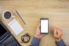Hombre que usa smartphone con los artículos esenciales de las herramientas del trabajo de oficina en o fotos de archivo libres de regalías