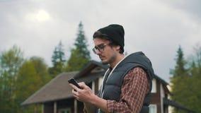 Hombre que usa smartphone en campo metrajes