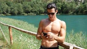 Hombre que usa smartphone en el lago imagenes de archivo