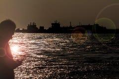 Hombre que usa smartphone en el puerto de transbordadores - contraluz Imagen de archivo