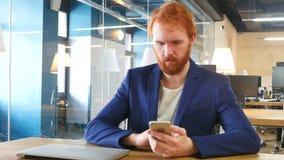 Hombre que usa Smartphone en el trabajo, pelos rojos almacen de video