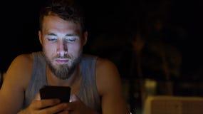 Hombre que usa smartphone en Internet de la ojeada de la noche imagenes de archivo