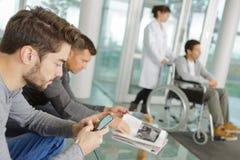 Hombre que usa smartphone en zona de espera del hospital imagen de archivo libre de regalías