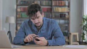 Hombre que usa Smartphone, hojeando en l?nea en el trabajo metrajes