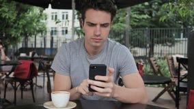 Hombre que usa Smartphone para hojear en línea almacen de video