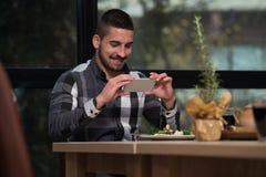 Hombre que usa Smartphone para tomar las fotos de la comida Imagen de archivo