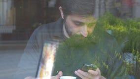 Hombre que usa su smartphone y bebiendo en una cafetería almacen de metraje de vídeo