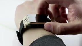 Hombre que usa su smartwatch app en el fondo blanco, nueva tecnología almacen de video