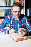 Hombre que usa su teléfono elegante móvil, libro en la tabla de madera Fotografía de archivo libre de regalías