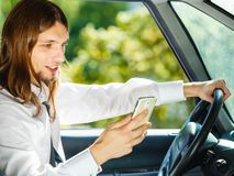 Hombre que usa su teléfono mientras que conduce el coche imágenes de archivo libres de regalías