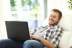 Hombre que usa un ordenador portátil que se sienta en un sofá Imagen de archivo libre de regalías