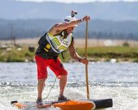 Hombre que usa un paddleboard para conseguir rio abajo Fotos de archivo