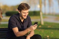 Hombre que usa un smartphone que se sienta en un banco en un parque Imagen de archivo