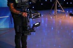 Hombre que usa un steadicam en un estudio de la televisión Foto de archivo libre de regalías