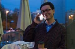 Hombre que usa un teléfono que manda un SMS en el smartphone app y que sostiene la taza de café de papel fotos de archivo libres de regalías