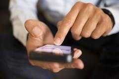 Hombre que usa un teléfono móvil en el sofá, interior Foto de archivo libre de regalías
