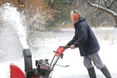 Hombre que usa un ventilador de nieve Imagen de archivo
