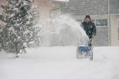 Hombre que usa un ventilador de nieve de gran alcance Imágenes de archivo libres de regalías