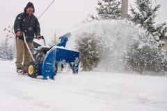 Hombre que usa un ventilador de nieve de gran alcance Fotos de archivo