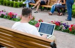 Hombre que usa una computadora portátil en un parque público Imágenes de archivo libres de regalías