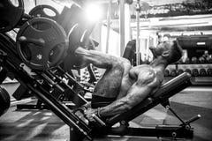 Hombre que usa una máquina de la prensa en un club de fitness Hombre fuerte que hace un ejercicio en sus pies en el simulador fotos de archivo