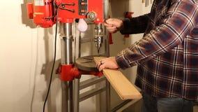 Hombre que usa una prensa de taladro para perforar un agujero en un pedazo de madera almacen de metraje de vídeo