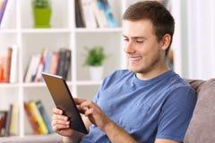 Hombre que usa una tableta en un sofá en casa Imagenes de archivo