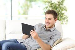 Hombre que usa una tableta que se sienta en un sofá Foto de archivo libre de regalías