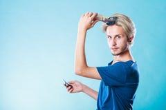 Hombre que va a afeitar su pelo largo Fotografía de archivo libre de regalías