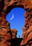 Hombre que va de excursión bajo arco con la luna Imagen de archivo libre de regalías