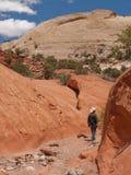 Hombre que va de excursión en barranca estrecha de la piedra arenisca roja Imagenes de archivo