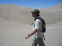 Hombre que va de excursión en dunas de arena Imagenes de archivo
