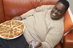 Hombre que ve la TV con la pizza en revestimiento Imagen de archivo